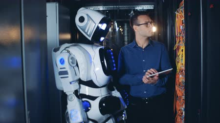 network server : Male IT programmer and robot, droid work at a data center.