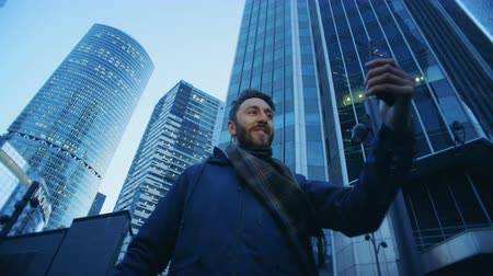 gritante : Tourist making a videocall standing near skyscrapers. Epic cinema camera shot.