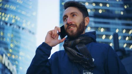 passer by : Young man talking on the phone and smiling. Epic cinema camera shot. Stock Footage