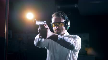 fire arms : A man aims with a gun at a shooting range, close up.