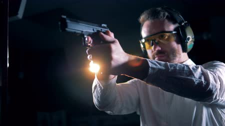 targeting : Man standing with a pistol in hands in a shooting room, shooting range. Stock Footage