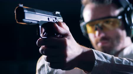 atirador : Male shooter holds a gun in a shooting room, close up. Stock Footage