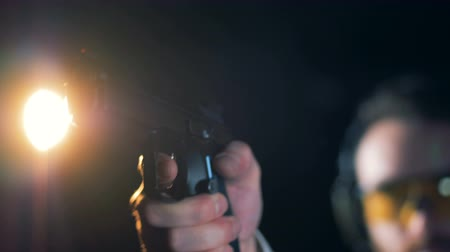 atirador : Shooter uses a pistol to aim, close up.