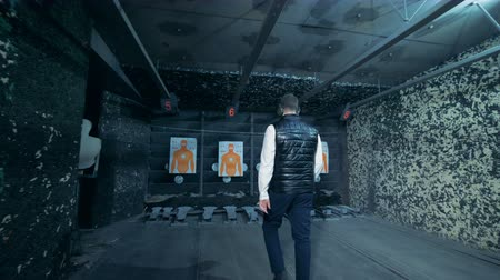 shooting range : One man looking at paper targets, back view. Stock Footage