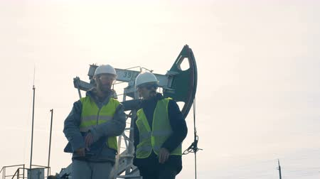 crude : Workers standing on an oil derrick background, close up. Stock Footage