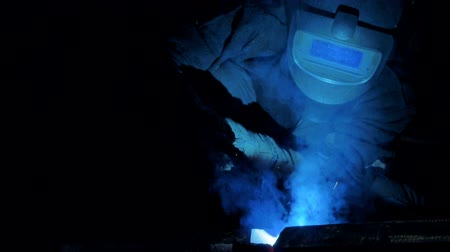 искра : Male welder working at a factory, close up.
