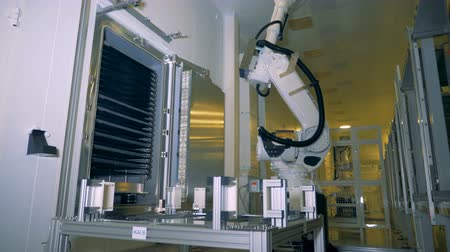 automatický : Factory equipment, robotic arm moving big solar panels, close up.