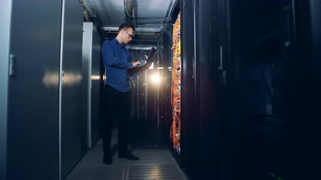 servis : IT specialist stands with a laptop in a server room, close up.