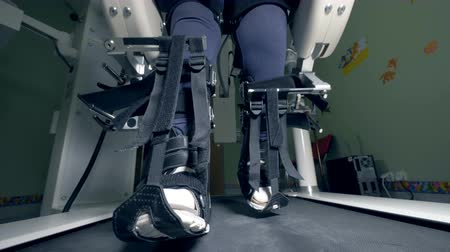 challenged : Legs of a physically challenged person tied with belts are moving along the walking track Stock Footage