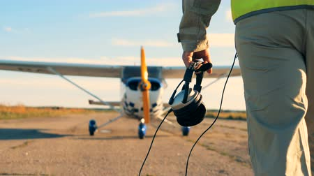 futópálya : Male pilot walking with headphones in hands, back view.