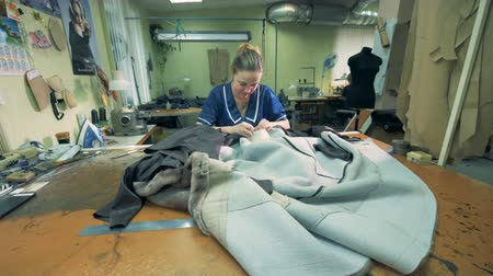 skins : Seamstress is sewing fur coats in a workshop Stock Footage