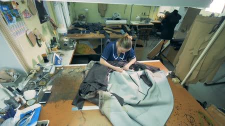 skins : Top view of a leather coat getting sewn by a female specialist