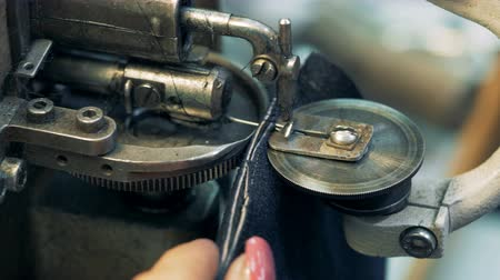 шитье дамского платья : Two pieces of fabric are getting sewn together by a sewing machine in a close up Стоковые видеозаписи