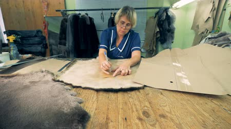 krawcowa : Seamstress is outlining contours on a furred skin