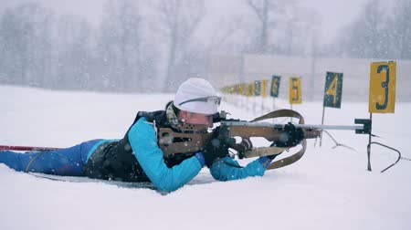mass start : Female biathlete is shooting in the middle of a biathlon training