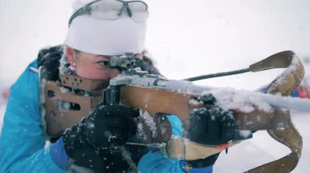 biathlon : Sportswoman is shooting from her riffle during a biathlon race in a lying position Stock Footage