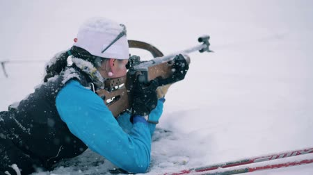 mass shooting : Snowbound shooting zone with a female biathlete firing Stock Footage
