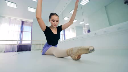 keep fit : Female ballet dancer is sitting in a split and stretching Stock Footage