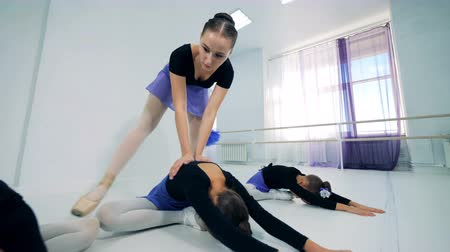 özel öğretmen : Female ballet teacher is helping girls to stretch Stok Video