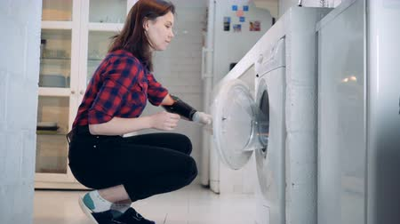 droid : Young woman with a bionic arm is taking clothes from the washing machine Stock Footage