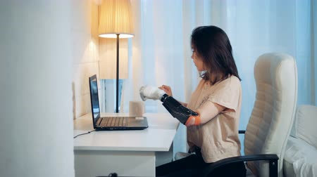 substitute : A lady is working on a laptop with her robotic hand and drinks coffee