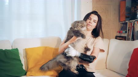 substitute : Young woman with a bionic hand is playing with her cat