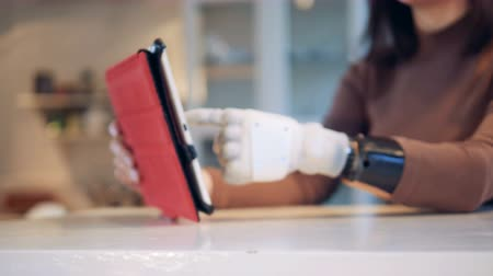 замена : Person types on a tablet with bionic hand, close up.