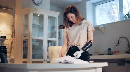 amputee : Handicapped woman turns pages with a robotic prosthesis, close up.