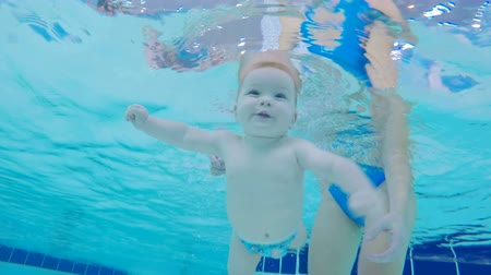 deep learning : Toddler learning to swim underwater in a pool, close up.