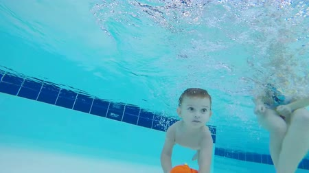 tomar : Baby takes a toy from the bottom of the pool, close up.
