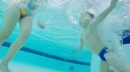 deep learning : A boy dives in a pool, learning to swim underwater, close up.