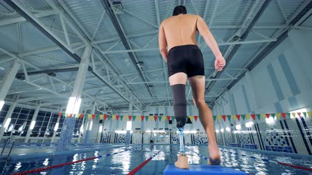 paralympics : Disabled man ready for swimming, back view.