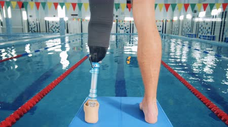 paralympics : Handicapped swimmer standing near a pool, close up.