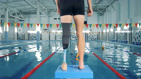 paralympics : Male swimmer with leg prosthesis, back view.