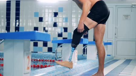 paralympics : A person puts on a prosthesis at a pool, side view. Stock Footage