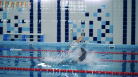 paralympics : Disabled swimmer jumps into a training pool, side view.