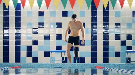 paralympics : Swimmer fixes his leg prosthesis after swimming, close up.