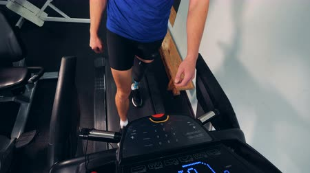 amputee : A man with prosthetic leg walks on a treadmill, close up. Stock Footage