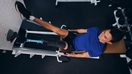 paralympic : A sportsman with a leg prosthesis training at a gym, top view. Stock Footage