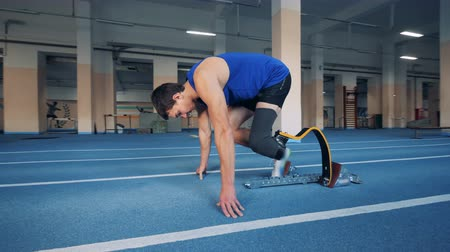 paralympic : Sprinter starts to run, wearing a leg prosthesis, side view.