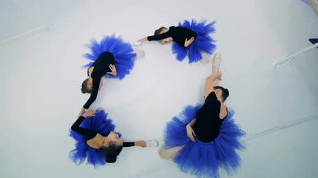 тапочка : Ballerinas stretching on a floor, top view.