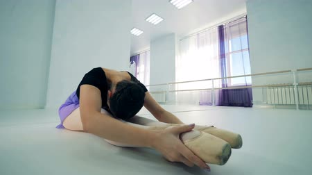 saia : One ballerina stretches her legs at a class, close up. Vídeos