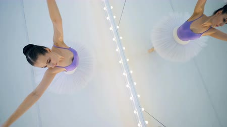 tiptoe : Ballet dancer spins near a mirror in a room, top view. Stock Footage