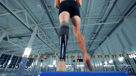 paralympics : A swimmer with a leg prosthesis, bottom view.