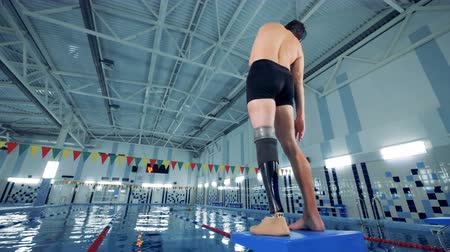 paralympics : A handicapped swimmer warming up near a pool, back view. Stock Footage