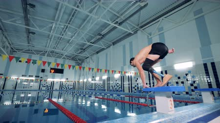paralympics : Swimmer with a leg prosthesis jumps into the pool, close up.