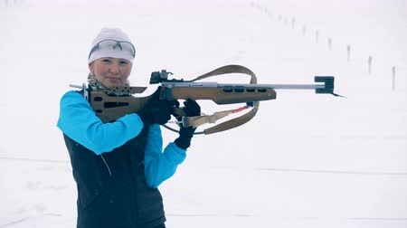 equipped : Sportswoman is ready to shoot during biathlon race