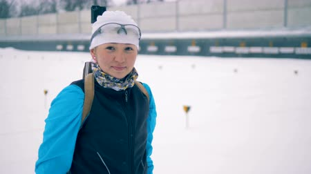biathlon : Lady athlete is smiling while putting on a rifle