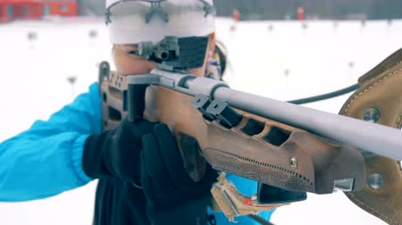 biathlon : A rifle with its muzzle in the hands of a female biathlete Stock Footage