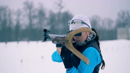 biathlon : Female biathlete is putting a rifle onto her back after aiming Stock Footage